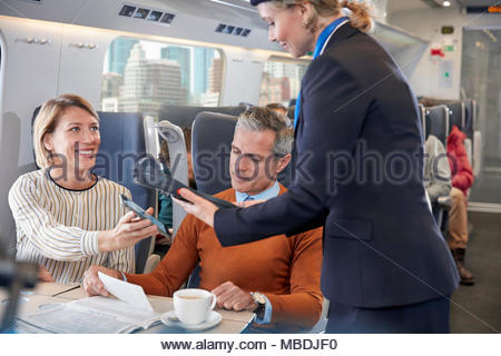 Woman with smart phone using contactless payment, paying attendant on passenger train - Stock Photo