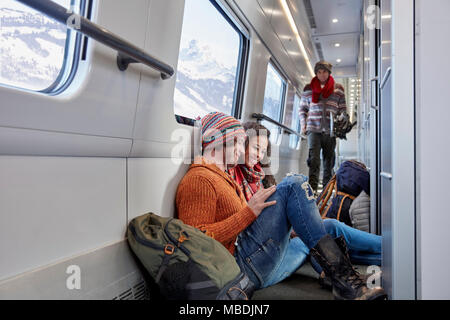 Young couple backpacking, riding passenger train - Stock Photo