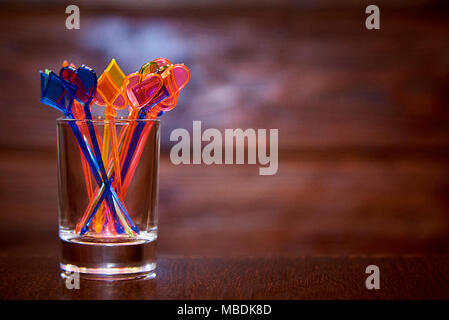 Multi-colored skewers for canapés in a glass cup on a wooden background. Copy space. - Stock Photo