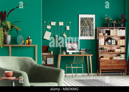 Green living room interior with books on wooden cupboard and desk for remote work - Stock Photo