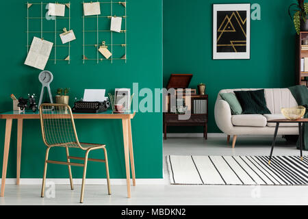 Gold, metal chair by a wooden desk with clock and typewriter in open space interior with carpet and bright sofa - Stock Photo