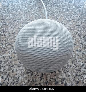 Overhead view of a Google Home Mini with cable. - Stock Photo