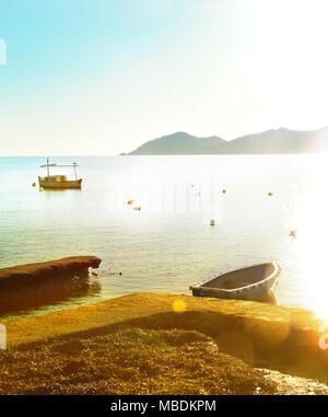 Fisherboat and sunset scene on Ibiza Island. Idyllic sundown scene with sea and coastline. - Stock Photo