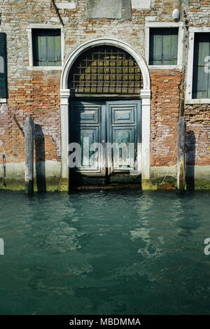 Facade of partially mossy old brick house with wooden vintage door - Stock Photo