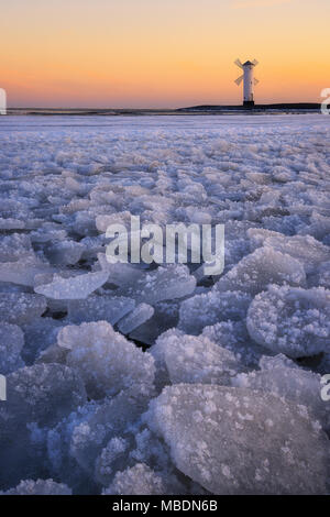 Dramatic Baltic sea scene. Cold icy morning. Frozen beach during sunrise. Beach covered by ice. Beautiful sunrise over a windmill-shaped lighthouse. S - Stock Photo