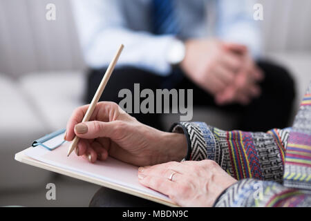Close-up of psychotherapist writing notes while analyzing her patient - Stock Photo