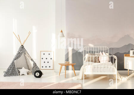 White child's bed against a wall with mountain wallpaper in bedroom interior with patterned tent - Stock Photo