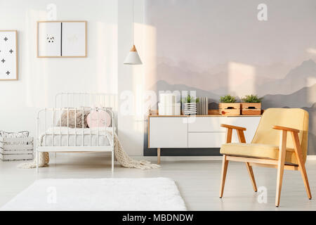 Yellow armchair and plants on white cupboard in child's bedroom interior with mountain pattern - Stock Photo