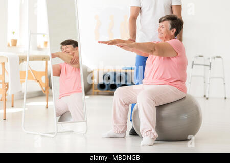Smiling senior exercising with a physiotherapist on a silver ball at a white gym - Stock Photo
