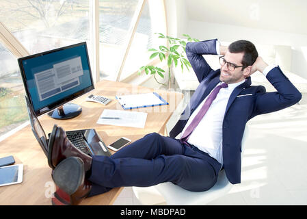 Full length shot of successful young businessman wearing suit while sitting at his modern office with his legs on office desk. - Stock Photo