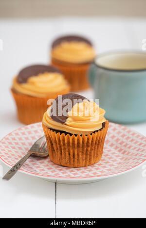 Colourful chocolate orange cupcakes on a plate with a mug of tea - Stock Photo