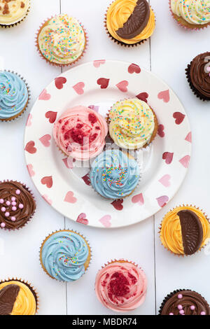 Colourful cupcakes on a heart pattern plate pattern - Stock Photo