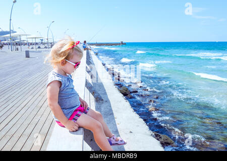 Blondy little baby girl 2-3 year old in pink sunglasses sitting alone on wooden sea railing on the seafront of Tel Aviv. Looking at swash. Childhood c - Stock Photo