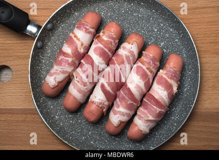Preparation of raw sausages wrapped spirally in bacon on a frying pan. Top view. - Stock Photo