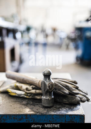 Closeup still life of gloves and a heavy duty hammer in a sheet metal factory. - Stock Photo