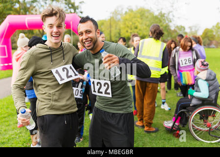 Portrait enthusiastic male runner friends with water hugging at charity run finish line in park - Stock Photo