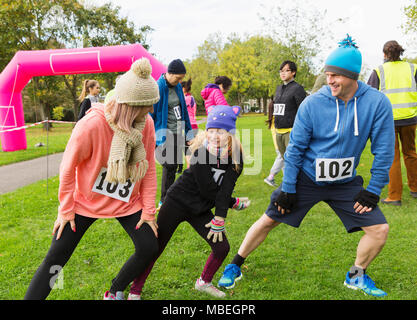 Family runners stretching, preparing for charity run in park - Stock Photo