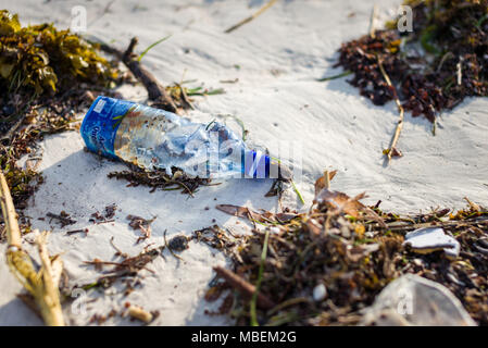 Plastic bottle waste lies washed up on the shore of a white sand beach - Stock Photo