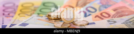 many banknotes of European currency laying under stacked coins - Stock Photo