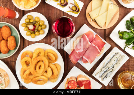 The food of Spain. An overhead photo of many different Spanish tapas, shot from above on a dark rustic texture. Jamon, cheese, wine, olives, croquette - Stock Photo