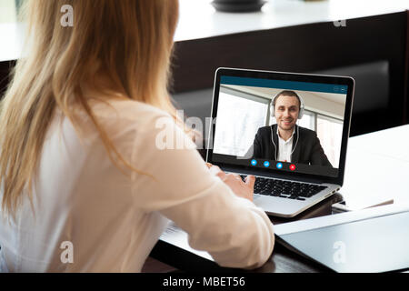 Businesswoman making video call to business partner using laptop. Close-up rear view of young woman having discussion with corporate client. Remote jo - Stock Photo