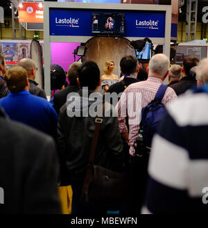 Photographers gather round a young beautiful model during a demonstration of lighting at the Photography Show at the NEC in Birmingham in March 2018 - Stock Photo