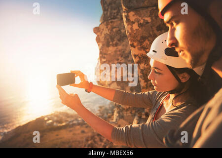 Rock climbers with camera phone photographing ocean view - Stock Photo