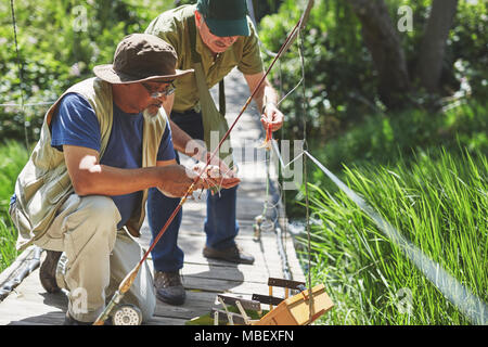 Active senior men friends preparing fishing line - Stock Photo