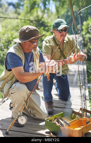Active senior male friends preparing fishing lines - Stock Photo