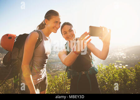 Female rock climbers taking selfie with camera phone - Stock Photo