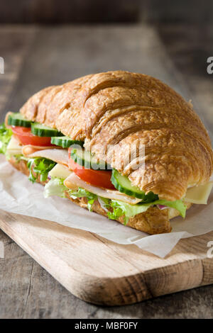 Croissant sandwich with cheese, ham and vegetables on wooden table - Stock Photo