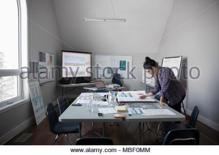 Female city planner reviewing blueprints, working in office - Stock Photo