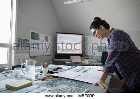 Female city planner reviewing blueprints in office - Stock Photo