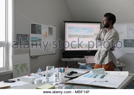 Thoughtful male city planner looking out window, working in office - Stock Photo