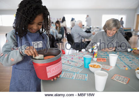 Girl selling fundraising raffle tickets at bingo in community center - Stock Photo
