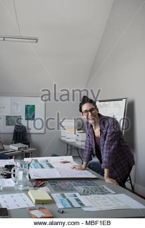 Portrait smiling, confident female city planner reviewing blueprints, working in office - Stock Photo