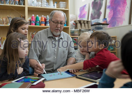 Senior volunteer and preschool students drawing with stylus and digital tablet in classroom - Stock Photo