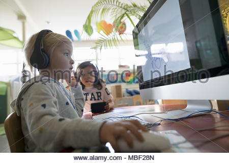 Preschool girl student wearing headphones, using computer in classroom - Stock Photo