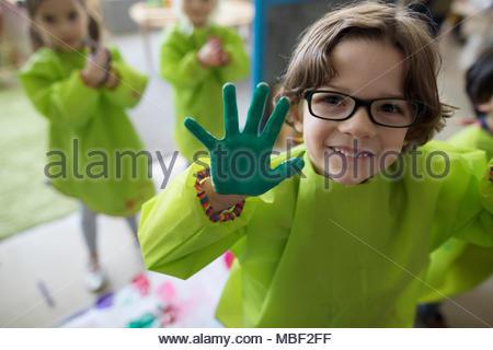 Portrait smiling, confident preschool boy in smock showing finger paint on hands - Stock Photo
