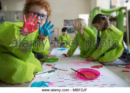 Portrait preschool boy in smock showing finger paint on hands at poster in classroom - Stock Photo