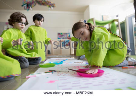 Preschool students in smocks using finger paints on poster in classroom - Stock Photo