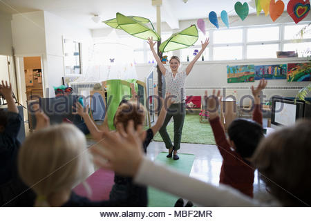 Preschool teacher and students practicing yoga tree pose in classroom - Stock Photo