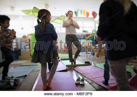 Preschool teacher and students practicing yoga tree pose in classroom - Stock Photo