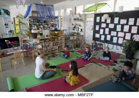 Preschool teacher and students practicing yoga in classroom - Stock Photo