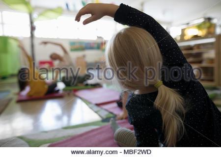 Preschool girl practicing yoga side bend in classroom - Stock Photo