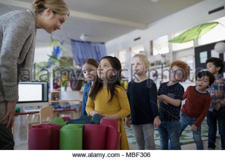Preschool teacher giving yoga mats to students in classroom - Stock Photo