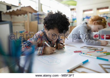 Focused preschool boy drawing letters with marker in classroom - Stock Photo