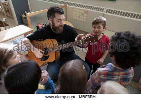 Male teacher with guitar teaching preschool students in classroom - Stock Photo