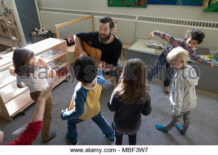 Preschool students dancing, listening to male teacher playing guitar in classroom - Stock Photo