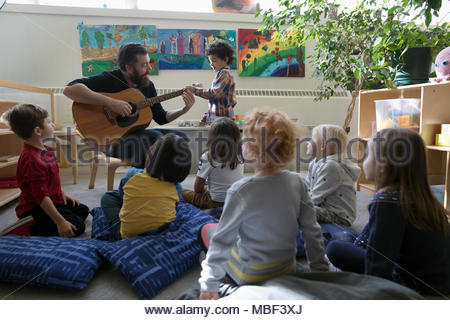 Preschool students listening to male teacher playing guitar in classroom - Stock Photo